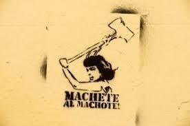 "black graffiti on yellow wall of a woman yielding a machete and words beneath that read ""Machete al Machote"""