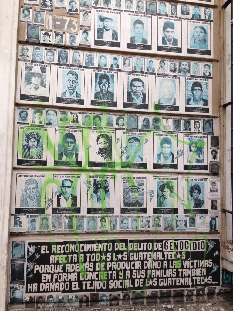 Photograph of a wall of the faces of people killed by the state during the Internal Armed Conflict in Guatemala.