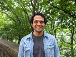 A photograph of Miguel, a smiling masc person with black hair, grey shirt, and a loose jean jacket.