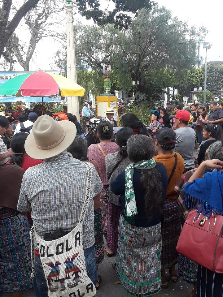 The march against the Amnesty Law in Chimaltenango began at the city's statue for Dignification of the Victims of the Internal Armed Conflict. Pictured: a crowd of people in front of a statue of a Mayan woman tearing apart a gun.