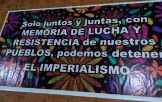 """Una pancarta que dice, """"Solo juntas y juntos, con MEMORIA DE LUCHA Y RESISTENCIA de nuestroa PUEBLOS, podemos detener EL IMPERIALISMO."""""""
