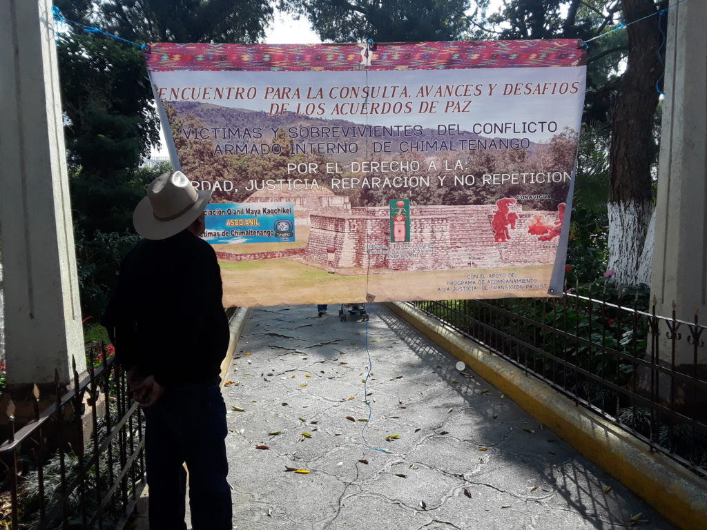 "A person looks at a sign that says: ""Victims and survivors of the Internal Armed Conflict in Chimaltenango for the right to truth, justice, reparations, and no repetition."""