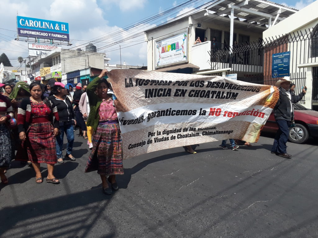 "Two people hold a sign that reads: ""Justice for the disappeared starts in Choatalúm / youth, may we guarantee that genocide is never repeated / for the dignity of the victims, Council of Widows from Choatalúm, Chimaltenango."""