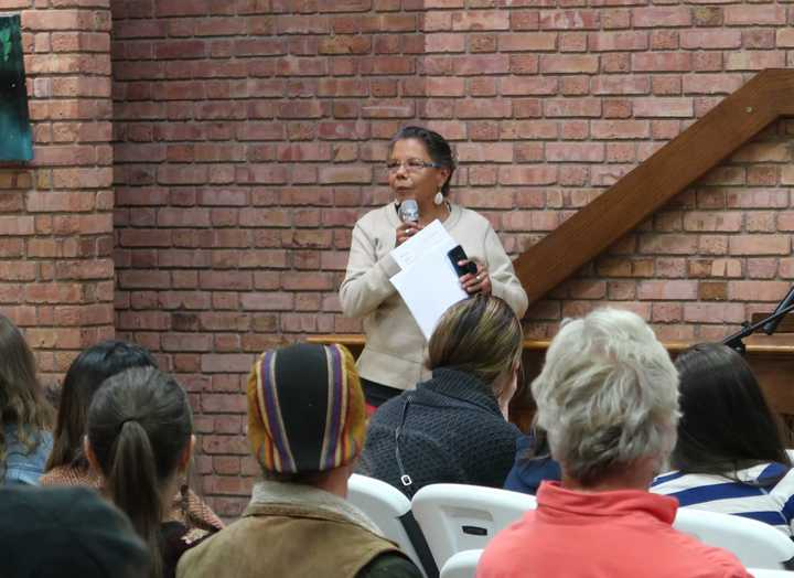 A photograph of an Ojibwe woman speaking into a microphone in front of many sitting people.