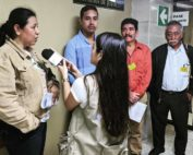 A journalist holds a microphone to a woman who is speaking while three men listen.